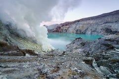 Siarka palił w krateru błękitnym jeziorze przy Kawah Ijen zdjęcia stock