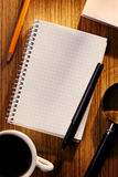Siatki filiżanka kawy na biurku i notatnik Obrazy Stock