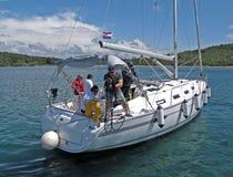 Sibenic, Chorwacja - mogą 8, 2015: Faceci cumuje żeglowanie jacht przy zatoką wyspa z zieleni wybrzeża szkoleniem jachting szkoła Fotografia Stock