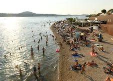 Sibenik Kroatien - Augusti 18, 2017: Folket vilar på stranden in Royaltyfri Foto