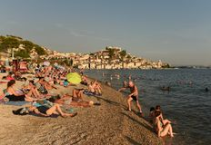 Sibenik Kroatien - Augusti 18, 2017: Folket vilar på stranden in Royaltyfria Foton