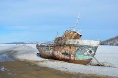 Siberië, meer Baikal, Olkhon-eiland, Kaap Khoboy, Rusland, 11 Maart, 2017 Oud roestig schip op de rand van de officiële ijsweg vo Stock Foto's