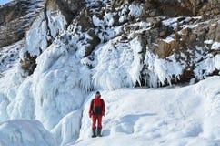 Siberia, lake Baikal, Olkhon island, Cape Khoboy, Russia, February, 22, 2017. Tourist walking near the ice build-up on the shore o Royalty Free Stock Photo