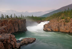 Siberia. Magic waterfall at Putorana plateau. 'Siberia. Magic waterfall at Putorana plateau on Dulismar river at a sunset. White stream between orange basalt stock photo