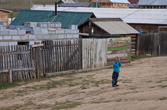 Siberian children. A shy child is playing in the street of a siberian village Royalty Free Stock Image