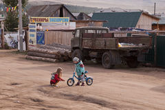 Siberian children. Two children are playing in the street of a siberian village Royalty Free Stock Image