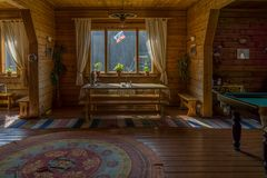 Siberian country house. Interior. Table with samovar kettle at the window, rugs on the floor and billiard table. Horizontal shot Royalty Free Stock Photos