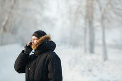 Siberian man talking on the phone outdoors by cold day in a warm winter down jacket with fur hood. Snow frost Stock Photos