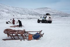 Siberian sledge, against the background of an all-terrain vehicle and people. Russia, Siberia, Yamal. Siberian sledge, against the background of an all-terrain Stock Photo