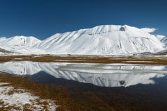 Sibillini山在与雪的水中反射了 库存照片