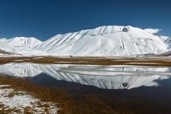 Sibillini berg reflekterade i vattnet med snö arkivfoton