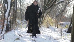 Sibirischer Junge mit einer Axt im Jungen des Wald A in einem Pelzmantel im Winter im Dorf stock video footage