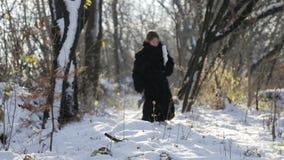 Sibirischer Junge mit einer Axt im Jungen des Wald A in einem Pelzmantel im Winter im Dorf stock footage