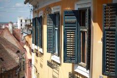 Sibiu amarillea la ventana verde constructiva con las persianas abiertas Fotos de archivo