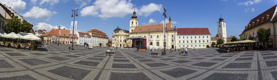 Sibiu central square panorama. Panoramic image of the central square in Sibiu, Romania with historic buildings and restaurants. Image taken on: August 3rd, 2015 stock photos