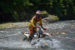 SIBIU, ROMÊNIA - 18 DE JULHO: Um copetitor na reunião dura de Red Bull ROMANIACS Enduro com uma motocicleta de KTM Foto de Stock