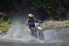 SIBIU, ROMÊNIA - 18 DE JULHO: Um copetitor na reunião dura de Red Bull ROMANIACS Enduro com uma motocicleta de KTM A reunião a ma Imagens de Stock