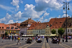 SIBIU, ROMANIA - JUNE 08, 2014: Tourists visit main square in Sibiu, Romania. Sibiu was designated a European Capital of Culture f Royalty Free Stock Photos