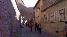 Sibiu, Romania. 12 November, 2015: People wander along the old backstreets with old fortified brick arcades and walls in the historic Lower Town of Sibiu city stock video footage