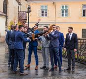 The groom`s friends hold him in front of the church in the Small Square. Sibiu city in Romania. Sibiu, Romania, October 07, 2017 : The groom`s friends hold him Stock Images