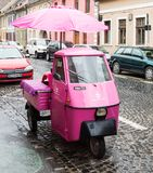 Pink scooter with closed cockpit and umbrella parked on the Timotei Popovich street in Sibiu city in Romania. Sibiu, Romania, October 07, 2017 : Pink scooter Stock Photography