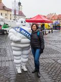 A tourist is photographed with a man dressed in a Michelin costume on the Large Square in Sibiu city in Romania. Sibiu, Romania, October 07, 2017 : A tourist is Royalty Free Stock Images