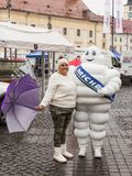 A tourist is photographed with a man dressed in a Michelin costume on the Large Square in Sibiu city in Romania. Sibiu, Romania, October 07, 2017 : A tourist is Stock Image