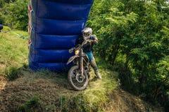 SIBIU RUMÄNIEN, JULI 16, 2016: En konkurrent på Gusterita Hillclimb fullföljande i Red Bull ROMANIACS hårda Enduro samlar Fotografering för Bildbyråer