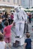 SIBIU RUMÄNIEN - 17 JUNI 2016: En fars skakar händer med en pojke i den stora fyrkanten under Sibiu internationell teaterfestival Arkivfoton