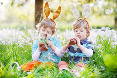 Sibling boys in Easter bunny ears eating chocolate Stock Photography