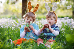 Sibling boys in Easter bunny ears eating chocolate Royalty Free Stock Images