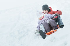 Sibling brother and little sister enjoying fast ride down snowy hill on orange snow slider Stock Images