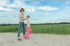 Sibling brother supporting his younger sister doing handstand on farm field dirt road stock photo