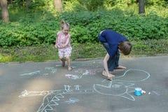Sibling children having fun during sidewalk chalking on asphalt surface stock image