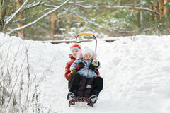 Sibling children having fun sliding down snowy hill during winter time Stock Photo