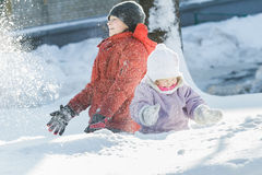 Sibling children making snowstorm by tossing up snow during frosty winter sunny day outdoors Stock Photos