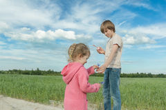 Sibling children sharing blue cornflowers and soap bubbles in green summer oat field Stock Photo