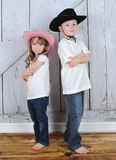 Sibling cowboy and cowgirl in sweet pose Stock Image
