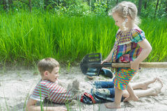 Sibling girl and boy digging on beach dune and burying each other in white sand at pinewood background Royalty Free Stock Photos
