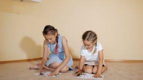 Sibling meisjes die met verven trekken stock footage