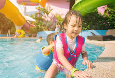 Sibling are playing in swimming pool Stock Photos