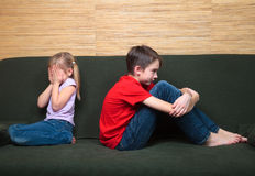 Sibling quarrel. Brother and sister  wearing casual clothes  sitting on a green couch back to back arter fight. Girl covers her face with hands Royalty Free Stock Photos