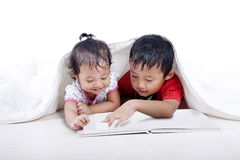 Sibling reading book under the blanket. Asian kids reading an empty book  on white Stock Photos