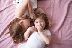 Sibling relationships, children's secrets, hug, close up, domest Stock Images