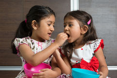 Sibling sharing food. Indian girls sharing food, murukku with each other. Asian sibling or children living lifestyle at home Stock Photos