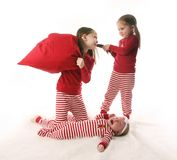 Sibling sister chaos. Three sisters dressed in Christmas pajamas. Two older girls are pulling hair and having a pillow fight while the baby is crying Royalty Free Stock Photos