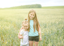 Sibling sisters hugging each in the field Royalty Free Stock Photography