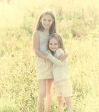 Sibling sisters hugging each in the field Stock Image