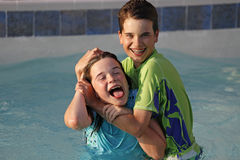 Siblings. A brother and sister wrestling in a swimming pool Stock Photos