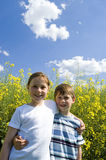 Siblings. Boy and girl arm in arm on a sunny day in front of a yellow blooming canola field Royalty Free Stock Photo